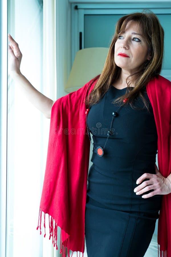 Όμορφη ώριμη γυναίκα που κοιτάζει από το παράθυρο στοκ φωτογραφία με δικαίωμα ελεύθερης χρήσης