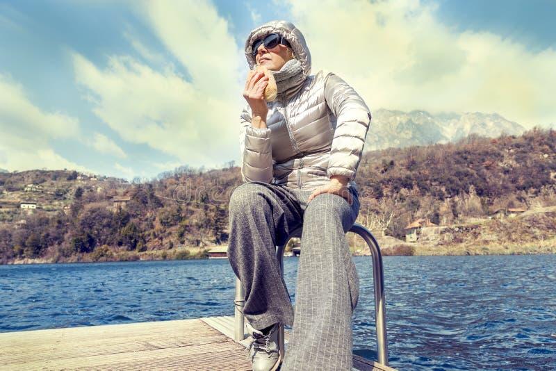 Όμορφη ώριμη γυναίκα που τρώει μια συνεδρίαση σάντουιτς στοκ φωτογραφίες με δικαίωμα ελεύθερης χρήσης