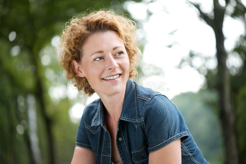 Όμορφη ώριμη γυναίκα που χαμογελά και που κοιτάζει μακριά στοκ φωτογραφίες με δικαίωμα ελεύθερης χρήσης