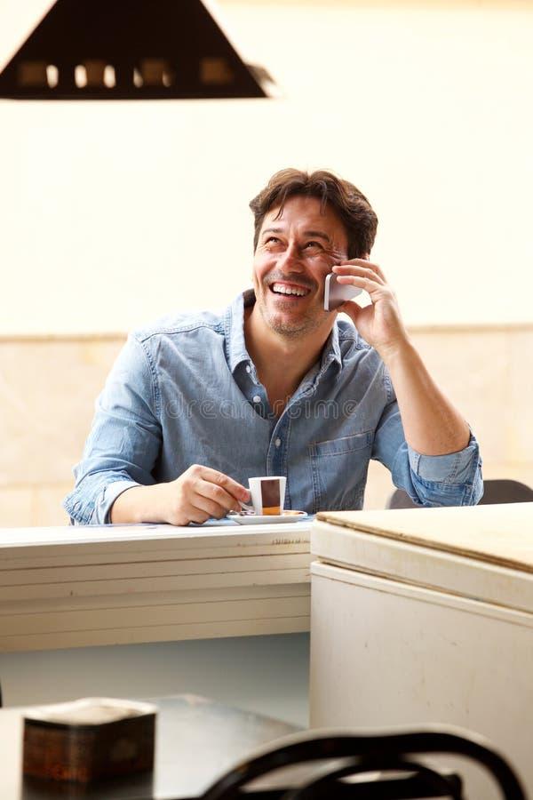 Όμορφη ώριμη συνεδρίαση ατόμων στον καφέ και ομιλία στο κινητό τηλέφωνο στοκ φωτογραφία με δικαίωμα ελεύθερης χρήσης
