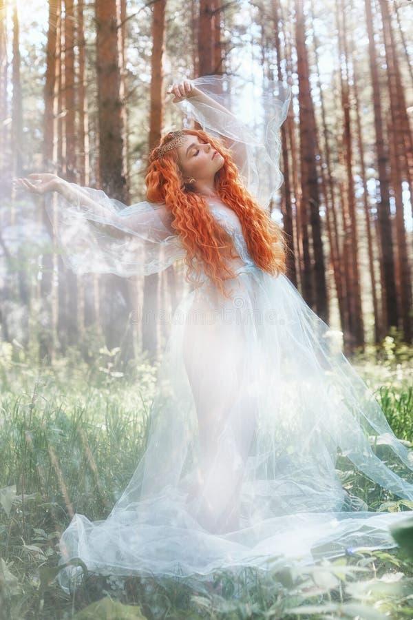 Όμορφη redhead δασική νύμφη γυναικών σε ένα μπλε διαφανές ελαφρύ φόρεμα στα ξύλα που περιστρέφουν στο χορό Κόκκινα κορίτσια τρίχα στοκ εικόνες