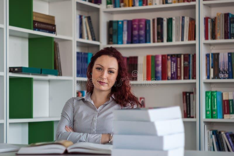 Όμορφη redhead συνεδρίαση κοριτσιών και σκέψη με τα βιβλία γύρω από τα WI στοκ φωτογραφία με δικαίωμα ελεύθερης χρήσης