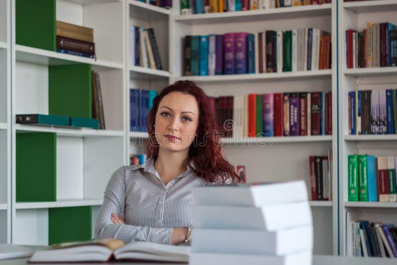 Όμορφη redhead συνεδρίαση κοριτσιών και σκέψη με τα βιβλία γύρω από τα WI στοκ φωτογραφία
