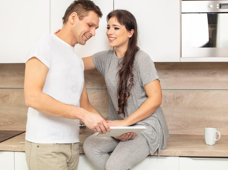 Όμορφοι γυναίκα και άνδρας πορτρέτου στην κουζίνα τους που κοιτάζουν στην ταμπλέτα στοκ εικόνα