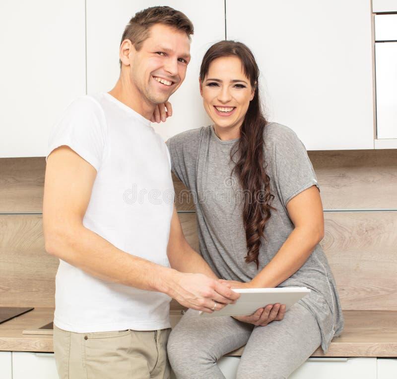 Όμορφοι γυναίκα και άνδρας πορτρέτου στην κουζίνα τους που κοιτάζουν στην ταμπλέτα στοκ εικόνες