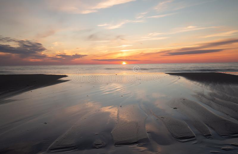 Όμορφοι ηλιοβασίλεμα και σχηματισμοί στην άμμο που γίνεται από το νερό του ωκεανού στοκ φωτογραφία με δικαίωμα ελεύθερης χρήσης