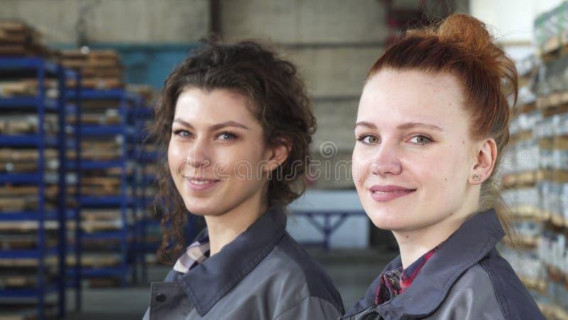 Όμορφοι θηλυκοί μηχανικοί που χαμογελούν στην τοποθέτηση καμερών στο εργοστάσιο στοκ φωτογραφία με δικαίωμα ελεύθερης χρήσης