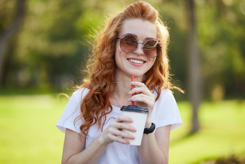 Όμορφοι κοκκινομάλλεις περίπατοι κοριτσιών μέσω του πάρκου με ένα φλιτζάνι του καφέ Το κορίτσι χαμογελά στη κάμερα Ένα κορίτσι στ στοκ φωτογραφίες με δικαίωμα ελεύθερης χρήσης