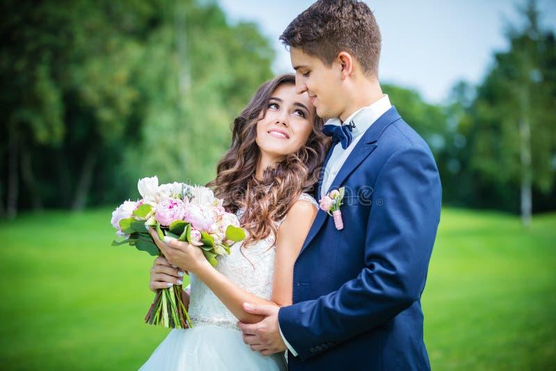 Όμορφοι νέοι νύφη και νεόνυμφος που πηγαίνουν να φιλήσει στοκ εικόνα