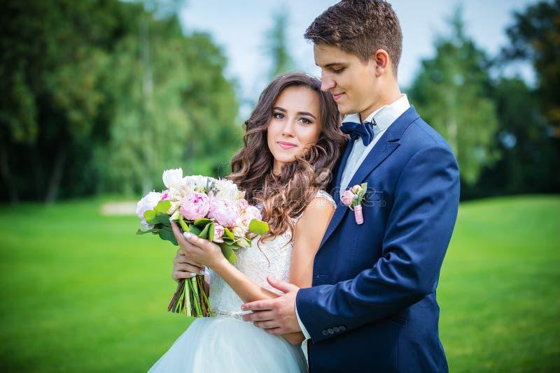 Όμορφοι νέοι νύφη και νεόνυμφος στο πάρκο στοκ φωτογραφίες