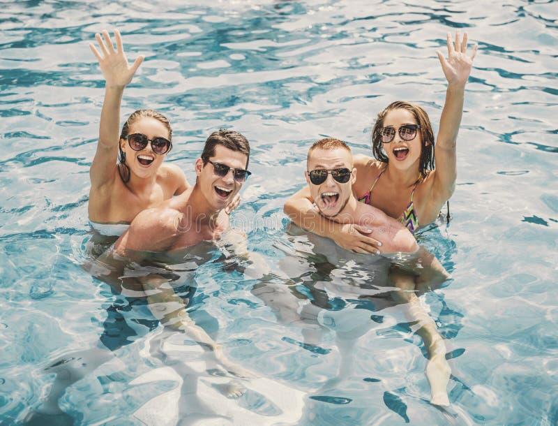 Όμορφοι νέοι που έχουν τη διασκέδαση στην πισίνα στοκ φωτογραφία