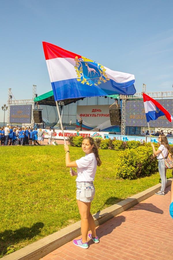Όμορφοι νέοι που κρατούν τις σημαίες της περιοχής της Samara στο ανάχωμα ποταμών του Βόλγα για διακοπές της φυσικής αγωγής στοκ φωτογραφία με δικαίωμα ελεύθερης χρήσης
