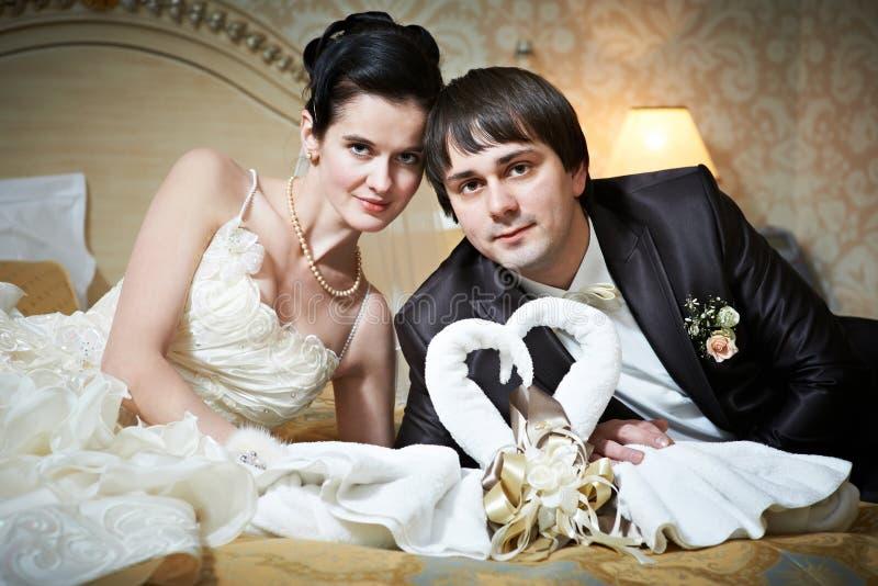 Όμορφοι νύφη και νεόνυμφος στην κρεβατοκάμαρα με τους κύκνους πετσετών στοκ εικόνες με δικαίωμα ελεύθερης χρήσης