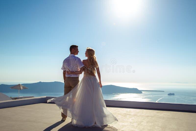 Όμορφοι νύφη και νεόνυμφος στη θερινή ημέρα γάμου τους στο ελληνικό νησί Santorini στοκ φωτογραφία