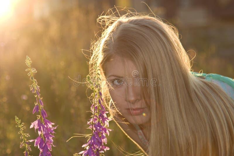 Όμορφοι ξανθός και λουλούδια στο ηλιοβασίλεμα στοκ φωτογραφία
