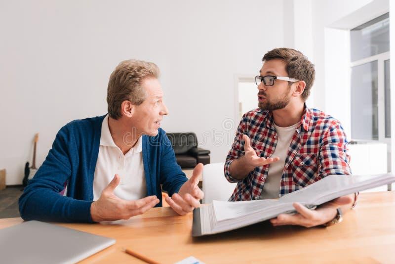 Όμορφοι συναισθηματικοί συνάδελφοι που κάθονται μαζί στον πίνακα στοκ εικόνες