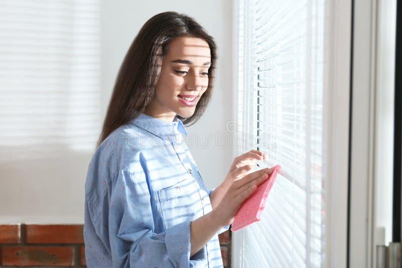 Όμορφοι τυφλοί παραθύρων γυναικών καθαρίζοντας με το κουρέλι στοκ εικόνες με δικαίωμα ελεύθερης χρήσης