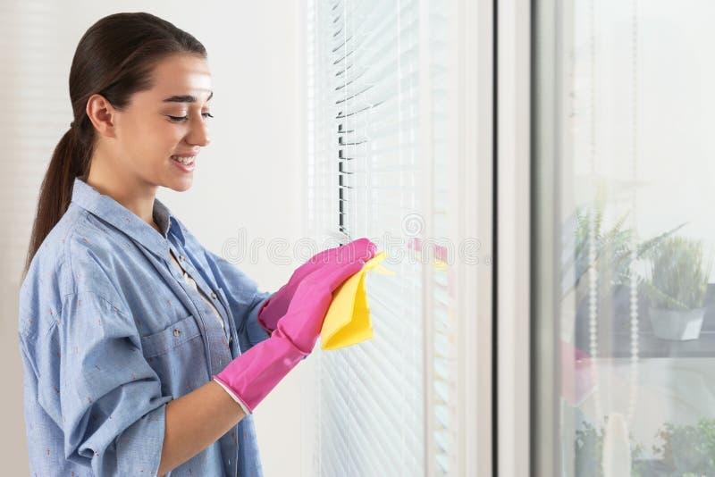 Όμορφοι τυφλοί παραθύρων γυναικών καθαρίζοντας με το κουρέλι στο εσωτερικό στοκ εικόνες με δικαίωμα ελεύθερης χρήσης