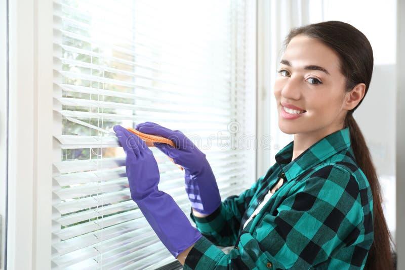 Όμορφοι τυφλοί παραθύρων γυναικών καθαρίζοντας με το κουρέλι στοκ φωτογραφίες