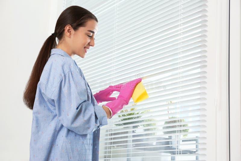 Όμορφοι τυφλοί παραθύρων γυναικών καθαρίζοντας με το κουρέλι στοκ φωτογραφία με δικαίωμα ελεύθερης χρήσης
