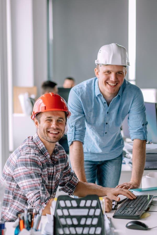 Όμορφοι χαμογελώντας αρχιτέκτονες που εργάζονται στο κτίριο γραφείων στοκ φωτογραφίες με δικαίωμα ελεύθερης χρήσης