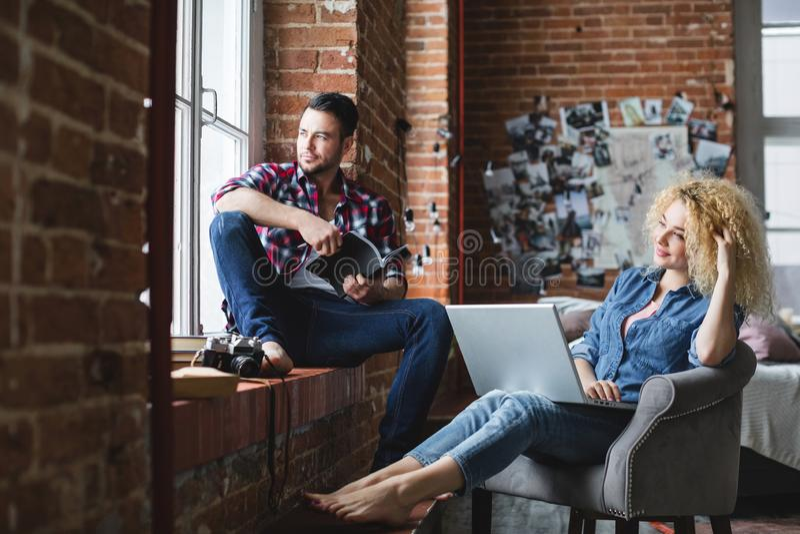 Όμορφος άνδρας και μια ελαφρύς-μαλλιαρή συνεδρίαση γυναικών σε μια πολυθρόνα σε ένα δωμάτιο με τους τουβλότοιχους στοκ φωτογραφίες με δικαίωμα ελεύθερης χρήσης