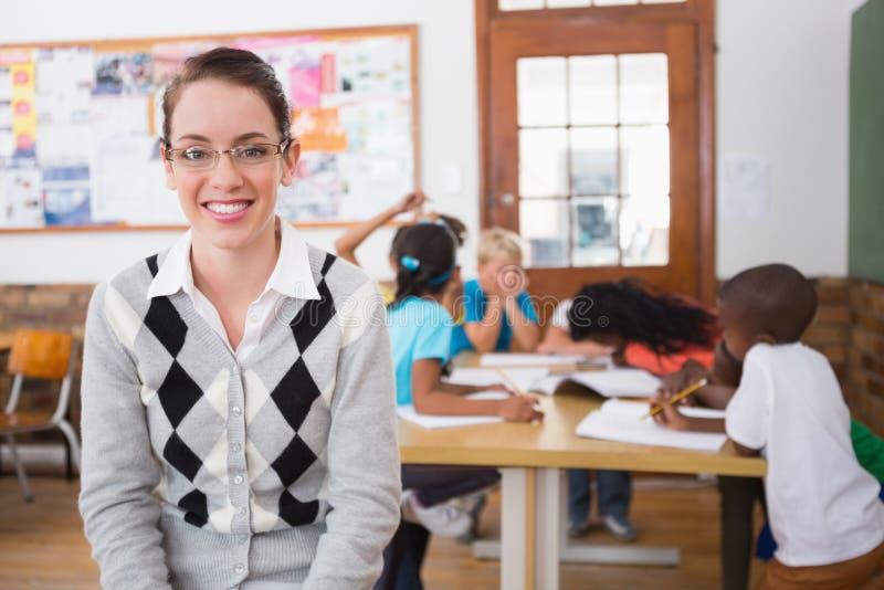 Όμορφος δάσκαλος που χαμογελά στη κάμερα στην κορυφή της τάξης στοκ φωτογραφία