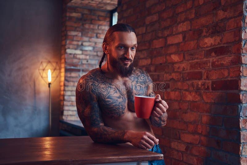 Όμορφος ένας γενειοφόρος το αρσενικό με ένα μοντέρνο κούρεμα και το μυϊκό σώμα, πίνει τον καφέ, που κλίνει σε έναν πίνακα στοκ φωτογραφία