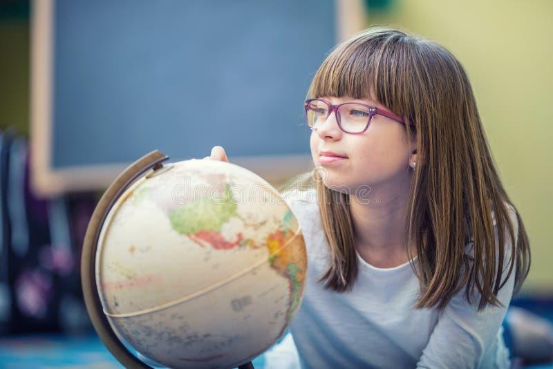 Όμορφος λίγο κορίτσι σπουδαστών που μελετά τη γεωγραφία με τη σφαίρα στο δωμάτιο ενός παιδιού στοκ εικόνες