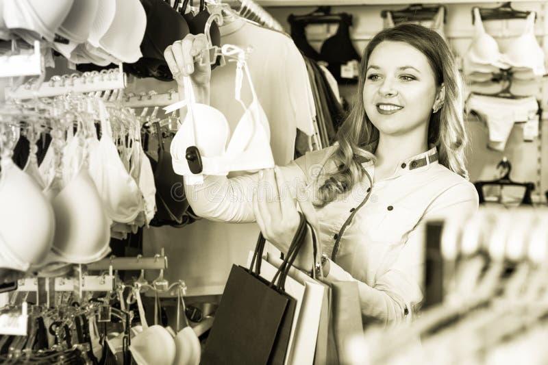 Όμορφος αγοραστής κοριτσιών που εξετάζει τους στηθοδέσμους στο κατάστημα στοκ φωτογραφία με δικαίωμα ελεύθερης χρήσης
