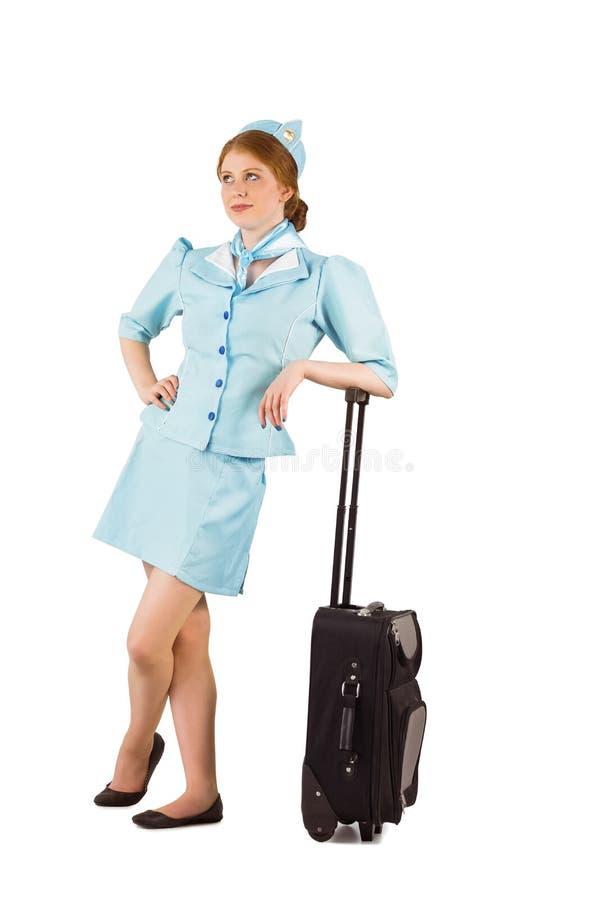 Όμορφος αεροσυνοδός που κλίνει στη βαλίτσα στοκ φωτογραφία