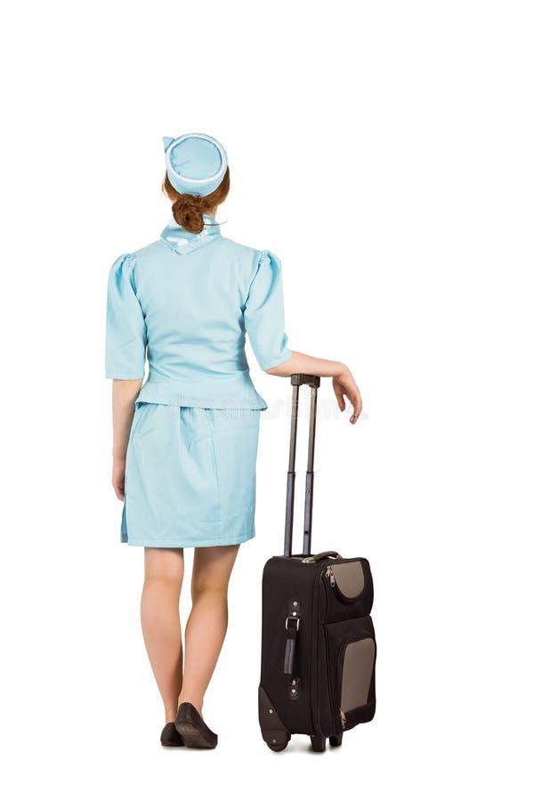 Όμορφος αεροσυνοδός που κλίνει στη βαλίτσα στοκ φωτογραφίες