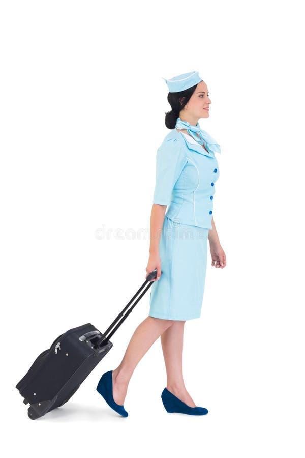 Όμορφος αεροσυνοδός που περπατά με τη βαλίτσα στοκ εικόνες