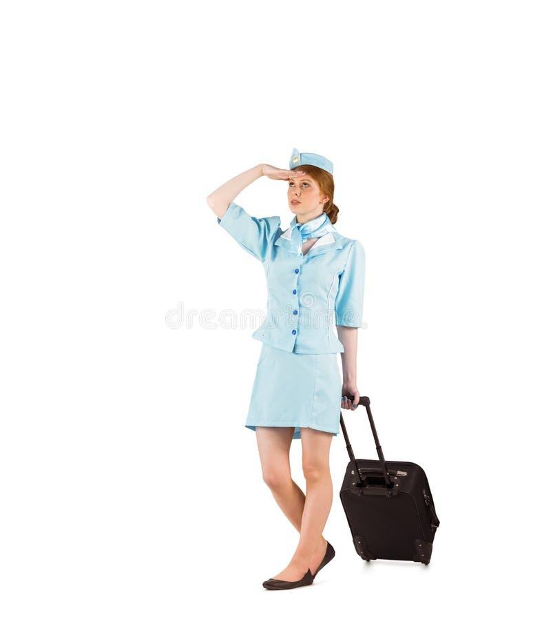 Όμορφος αεροσυνοδός που τραβά τη βαλίτσα στοκ εικόνες