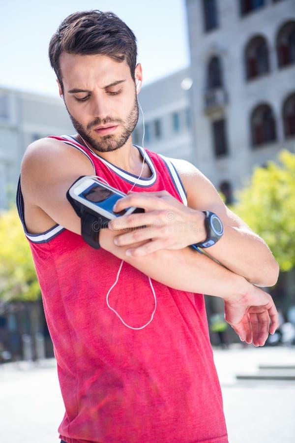 Όμορφος αθλητής που ρυθμίζει armband του στοκ εικόνες