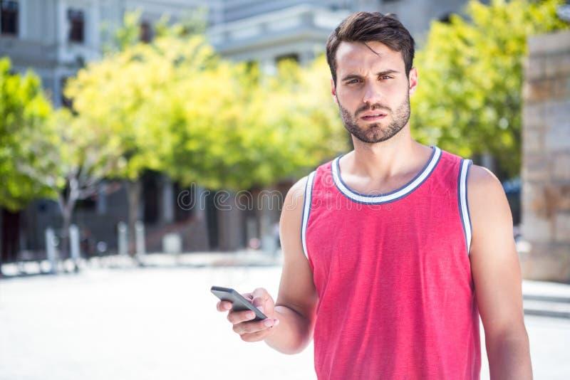Όμορφος αθλητής που στέλνει ένα κείμενο στοκ φωτογραφίες με δικαίωμα ελεύθερης χρήσης