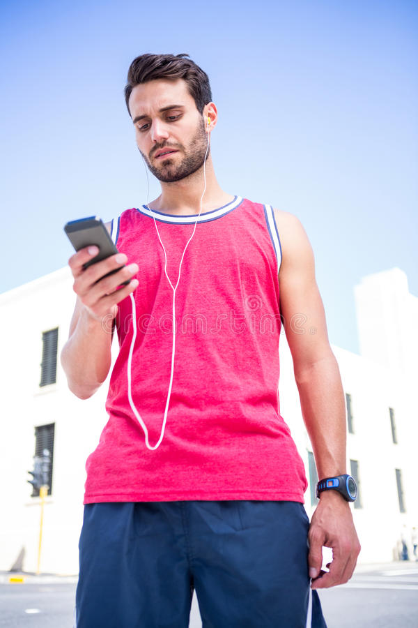 Όμορφος αθλητής που στέλνει ένα κείμενο στοκ φωτογραφία