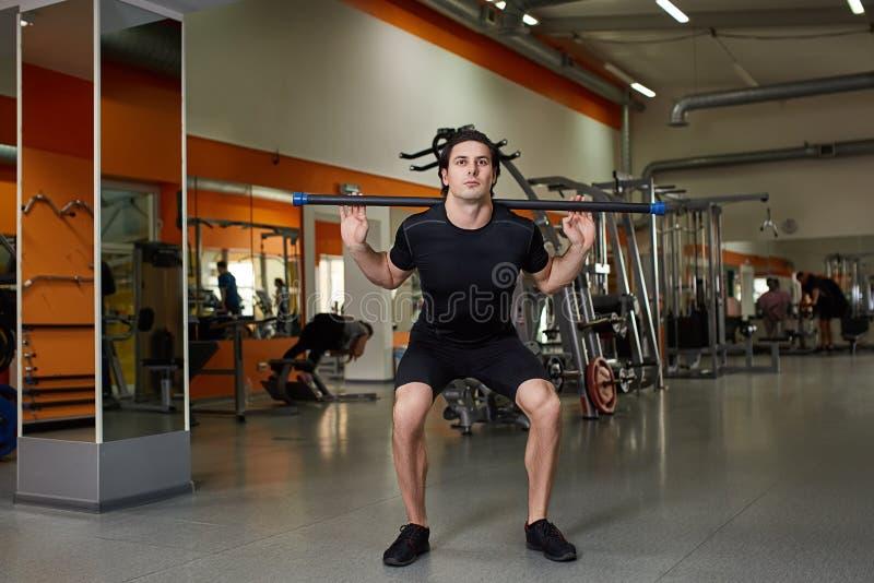 Όμορφος αθλητικός τύπος στο Μαύρο sportwear με τους μυς κάμψης φραγμών στη γυμναστική στοκ φωτογραφία με δικαίωμα ελεύθερης χρήσης