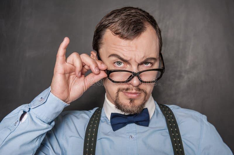 Όμορφος ακριβής δάσκαλος eyeglasses που εξετάζει σας στοκ εικόνες