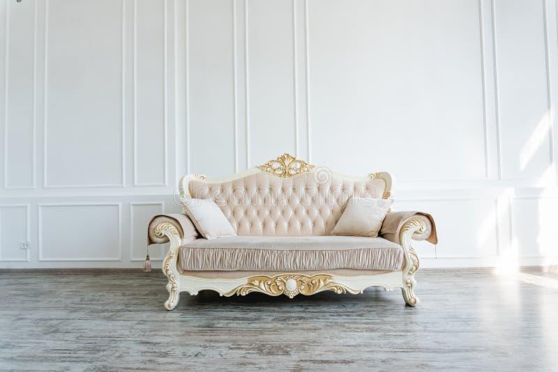 Όμορφος ακριβός μπεζ καναπές ενάντια σε έναν άσπρο τοίχο σε ένα κενό δωμάτιο στοκ εικόνες