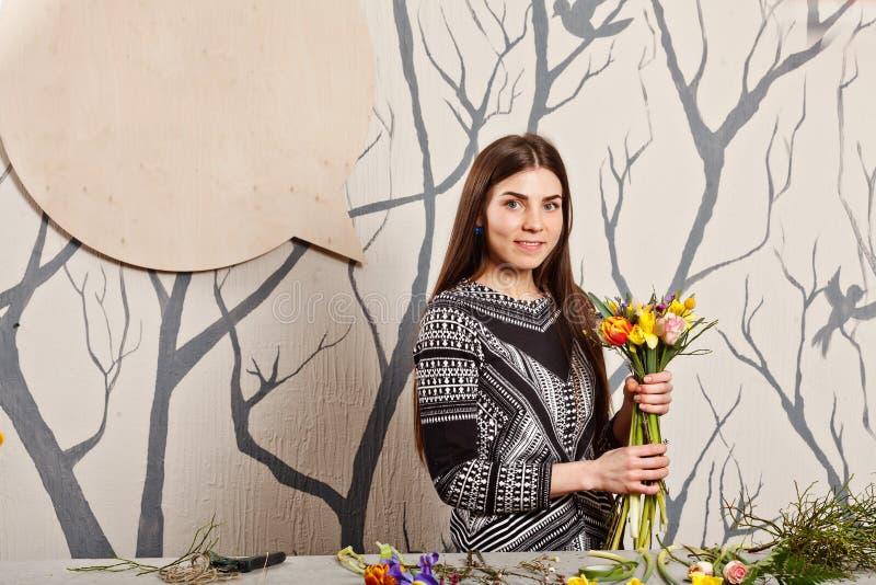 Όμορφος ανθοκόμος που κάνει την ανθοδέσμη από τα λουλούδια άνοιξη στοκ εικόνες