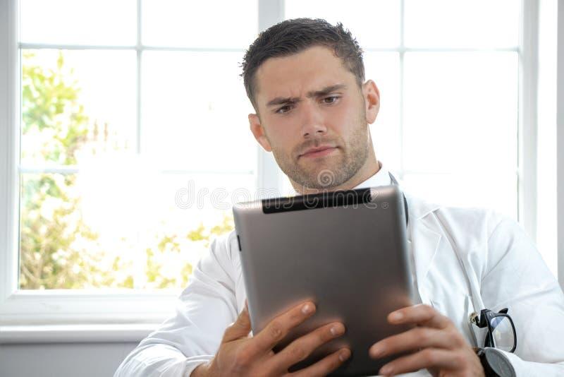 Όμορφος αρσενικός γιατρός στο άσπρο παλτό εργαστηρίων που κρατά την ψηφιακή ταμπλέτα στοκ φωτογραφία
