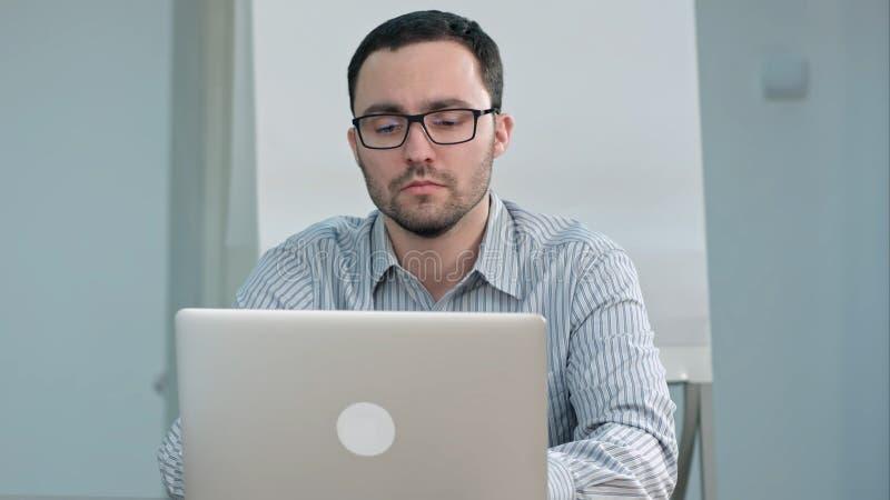 Όμορφος αρσενικός δάσκαλος στα γυαλιά που δακτυλογραφεί στο lap-top στοκ εικόνες με δικαίωμα ελεύθερης χρήσης