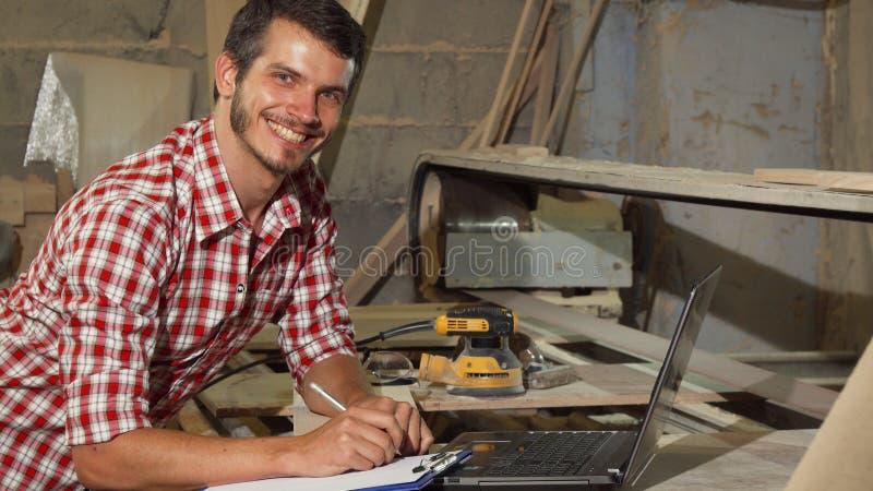 Όμορφος αρσενικός ξυλουργός που χαμογελά στη κάμερα στο εργαστήριό του στοκ εικόνες με δικαίωμα ελεύθερης χρήσης