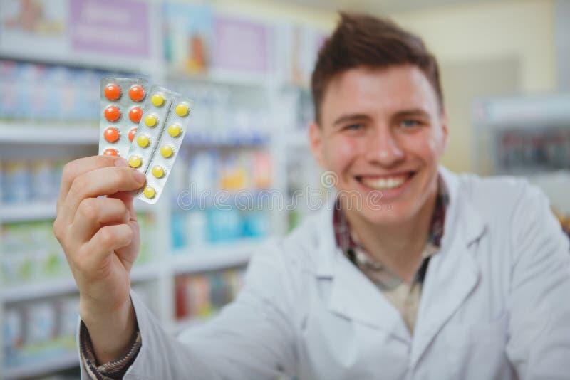 Όμορφος αρσενικός φαρμακοποιός που εργάζεται στο φαρμακείο του στοκ φωτογραφίες