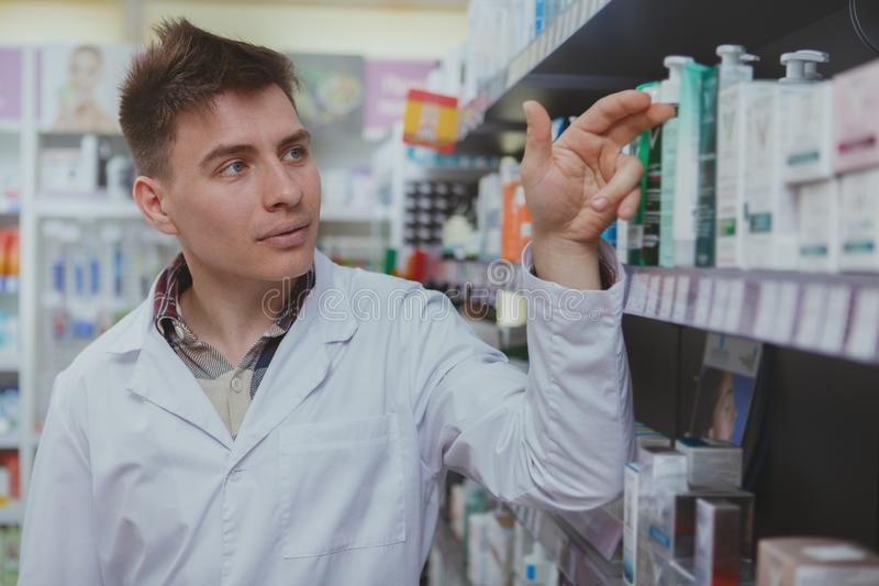 Όμορφος αρσενικός φαρμακοποιός που εργάζεται στο φαρμακείο του στοκ εικόνα