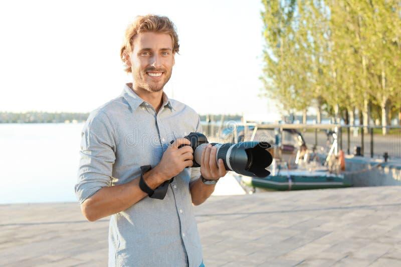 Όμορφος αρσενικός φωτογράφος που κρατά την επαγγελματική κάμερα στην αποβάθρα στοκ εικόνες με δικαίωμα ελεύθερης χρήσης