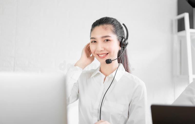 Όμορφος ασιατικός σύμβουλος γυναικών που φορά την κάσκα μικροφώνων του τηλεφωνικού χειριστή υποστήριξης πελατών στον εργασιακό χώ στοκ φωτογραφία με δικαίωμα ελεύθερης χρήσης