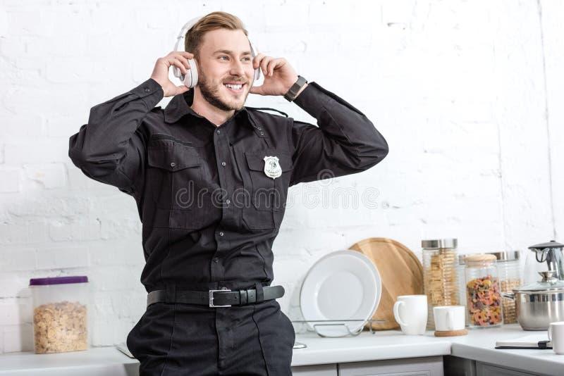 Όμορφος αστυνομικός που ακούει τη μουσική με τα ακουστικά στοκ φωτογραφίες