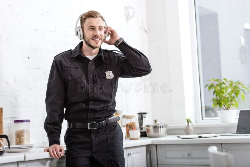Όμορφος αστυνομικός που ακούει τη μουσική με τα ακουστικά στοκ φωτογραφίες με δικαίωμα ελεύθερης χρήσης